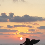 פסל של מלאך על רקע שקיעה