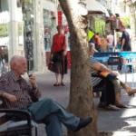 איש זקן יושב על ספסל ברחוב
