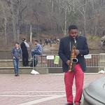 בחור שחור מנגן סקסופון בפארק